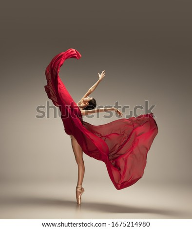 Free flight. Graceful classic ballerina dancing on grey studio background. Deep red cloth. The grace, artist, movement, action and motion concept. Looks weightless, flexible. Fashion, style. #1675214980