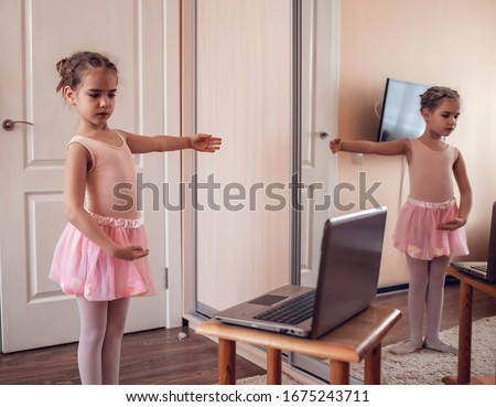 Pretty young ballerina practicing classic choreography during online class in ballet school, social distance during quarantine, self-isolation, online education concept #1675243711