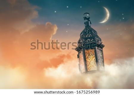 Ornamental Arabic lantern with burning candle glowing at night. Festive greeting card, invitation for Muslim holy month Ramadan Kareem. #1675256989