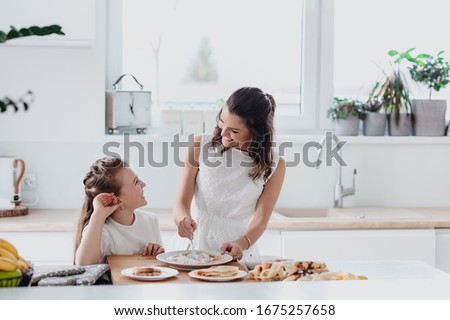 Young au pair making pancakes, cooking, baking in the white kitchen with a little girl  Royalty-Free Stock Photo #1675257658