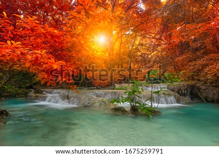 A beautiful waterfall deep in the tropical forest steep mountain adventure in the rainforest. Colorful leaves in autumn. #1675259791