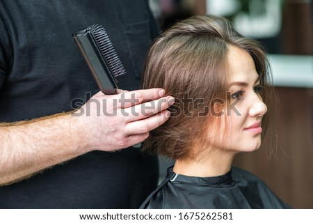 Hairdresser combs hair of woman at hair salon. #1675262581