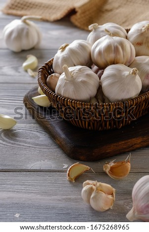 Healthy and wholesome food. Fresh garlic in a wicker basket on a wooden table #1675268965