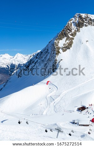 Panorama of ski resort with high snowy mountain view flying paraglider above chairlifts and riders  - nature and sport background, winter landscape. Vertical image Pic made on Krasnaya polyana, Sochi