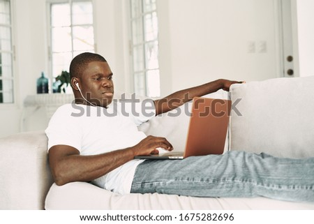 A man of African appearance at home with a laptop communicating #1675282696