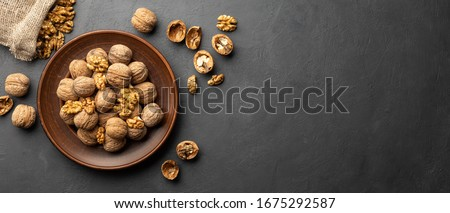 Nuts. Walnut kernels and whole walnuts on dark stone table. Black background. Top view, flat lay with copy space. #1675292587