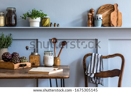 Stylish composition of kitchen interior with wooden family table, vegetables, herbs, plants, food supplies and kitchen accessories in gray concept of home decor.