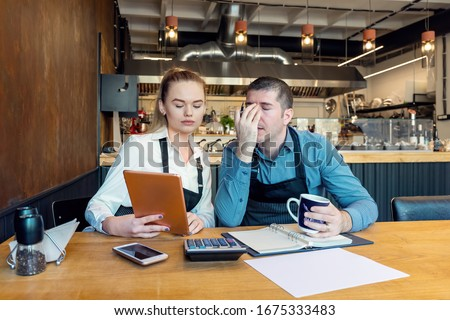 Worried owners in empty restaurant calculating finances - Coronavirus pandemic crisis - Bankrupt concept of Small entrepreneurs SME - Overwhelmed young woman and man with headache Royalty-Free Stock Photo #1675333483