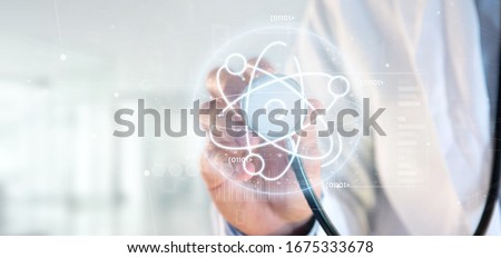 View of a Doctor holding an atom icon surrounded by data Royalty-Free Stock Photo #1675333678