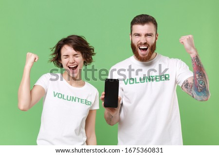 Joyful friends couple in volunteer t-shirt isolated on green background. Voluntary free work assistance help charity grace teamwork concept. Hold mobile phone with empty screen, doing winner gesture
