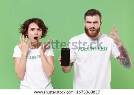 Perplexed young friends couple in white volunteer t-shirt isolated on green background. Voluntary free work assistance help charity grace teamwork concept. Hold mobile phone with blank empty screen