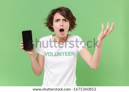 Shocked woman in volunteer t-shirt isolated on pastel green background. Voluntary free work assistance help charity grace teamwork concept. Hold mobile phone with blank empty screen spreading hands