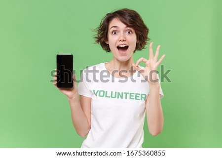 Excited girl in volunteer t-shirt isolated on pastel green background. Voluntary free work assistance help charity grace teamwork concept. Hold mobile phone with blank empty screen showing OK gesture