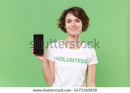 Smiling young brunette woman in volunteer t-shirt isolated on pastel green background. Voluntary free work assistance help charity grace teamwork concept. Hold mobile phone with blank empty screen