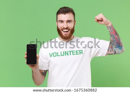 Strong man in volunteer t-shirt isolated on pastel green background. Voluntary free work assistance help charity grace teamwork concept. Hold mobile phone with empty screen, showing biceps, muscles