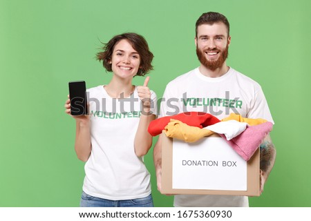 Friends couple in volunteer t-shirt isolated on green background. Voluntary free work assistance help charity grace. Hold donation box with clothes, mobile phone with blank screen, showing thumb up