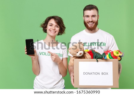 Smiling friends couple in volunteer t-shirt isolated on green background. Voluntary free work assistance help charity grace teamwork. Hold donation box with kids toys, mobile phone with empty screen