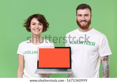 Smiling two friends couple in white volunteer t-shirt isolated on green background. Voluntary free work assistance help charity grace teamwork concept. Hold laptop pc computer with blank empty screen
