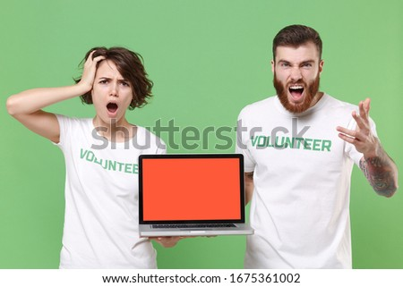 Shocked nervous friends couple in volunteer t-shirt isolated on green background. Voluntary free work assistance help charity grace teamwork. Hold laptop pc computer with blank empty screen screaming