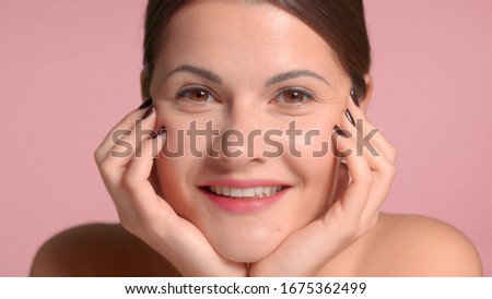 Nice pretty brunette with hands support her face watching to the camera and smiling. Pink background, natural makeup #1675362499