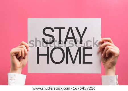 """Woman's hands holding paper with text """"stay home"""", protect from Coronavirus or Covid-19 epidemic #1675459216"""