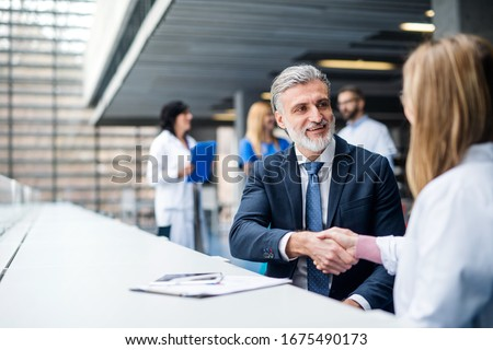 Doctors talking to pharmaceutical sales representative, shaking hands. Royalty-Free Stock Photo #1675490173