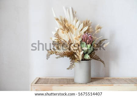 Minimalistic composition of dried flowers in cylindrical ceramic vase as home decoration.  Royalty-Free Stock Photo #1675514407