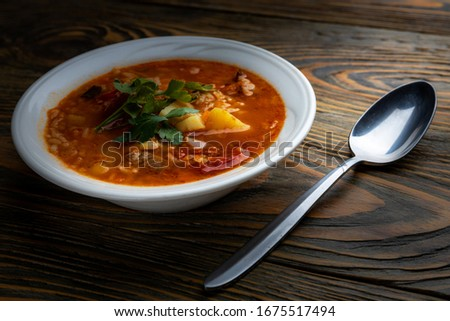 Kharcho soup with meat and rice on a wooden table, closeup, shallow depth of field. Concept, healthy food. #1675517494