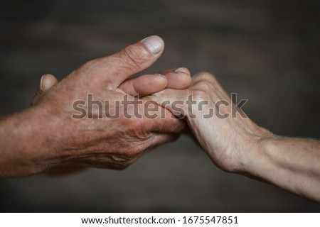 Granddaughter and grandfather holding hands close up  #1675547851