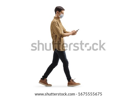 Full length profile shot of a young man with a medical face mask walking and typing on a mobile phone isolated on white background #1675555675