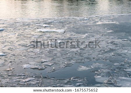 floating ice floes on the river in the spring season. Ice melts on the river. Frozen river #1675575652