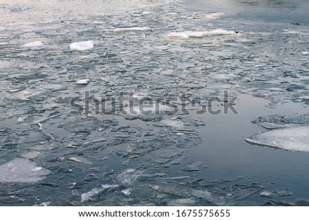 floating ice floes on the river in the spring season. Ice melts on the river. Frozen river #1675575655