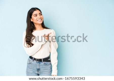 Young indian woman isolated on blue background smiling and pointing aside, showing something at blank space. #1675593343