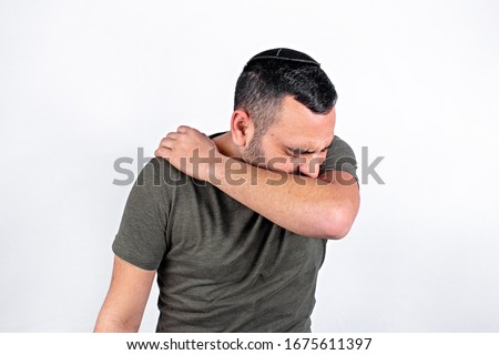 A handsome Jewish guy coughs into the elbow Royalty-Free Stock Photo #1675611397