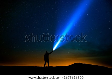 Man with flashlight pointed at the starry sky Royalty-Free Stock Photo #1675616800