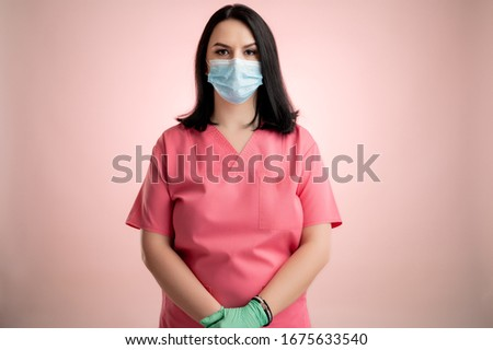 Portrait of beautiful woman doctor with stethoscope wearing pink scrubs, with protective mask posing on a pink isolated backround. #1675633540