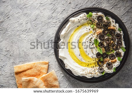 """Arabic Cuisine: Middle Eastern delicious dip """"Labneh"""". Cream cheese dip with olive oil, herbs and olives served with traditional pita bread. Top view with copy space. #1675639969"""