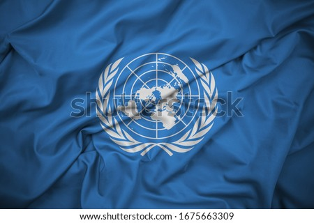 United Nations Flag. Official emblem of the UN in white on a blue background. Silk Fabric Royalty-Free Stock Photo #1675663309