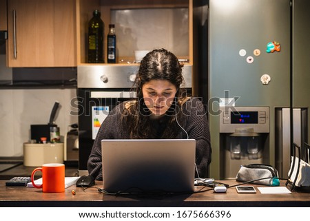 Young spanish girl teleworking at home because of the restrictions given by spanish government due to coronavirus COVID-19 sanitary crysis #1675666396