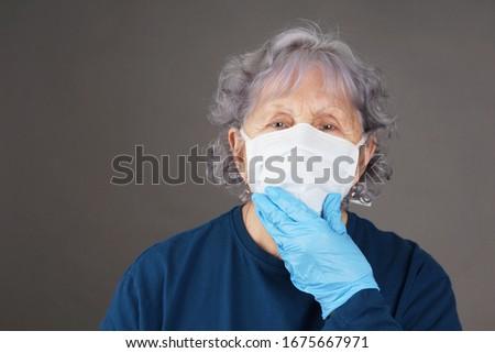Senior woman wearing protective mask and glove, coronavirus COVID-19 pandemic #1675667971