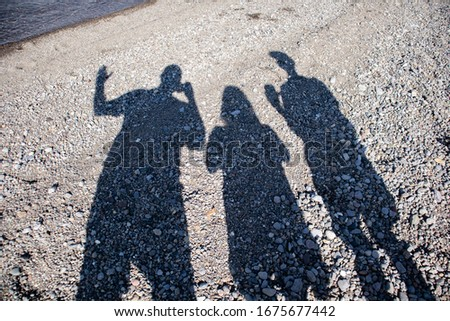 Three people taking shadow pics with their smart phones on the beach at Yellowstone Lake in Wyoming