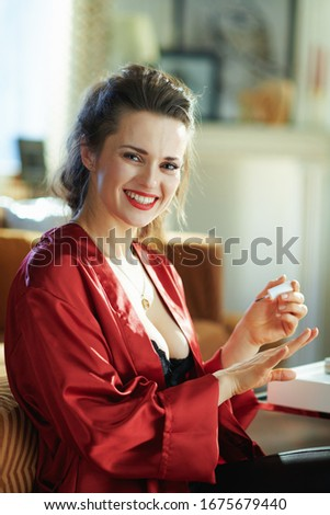 happy modern housewife in black body lingerie and red bathrobe at modern home in sunny day applying nail polish. #1675679440