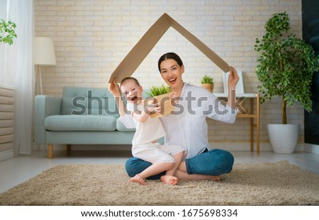 Mother and child girl in the room with a symbol of roof. Concept of housing for young family.  #1675698334