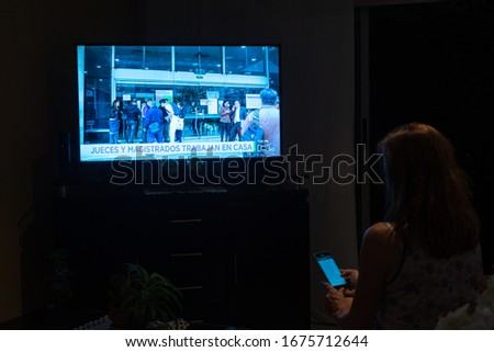 Cali, Colombia - March 16, 2020: woman in quarantine checking the smartphone and watching news about the COVID-19 virus. #1675712644