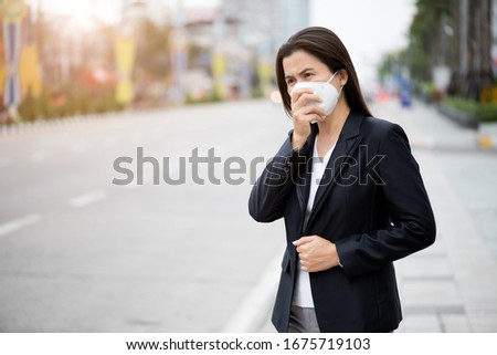 Close up of a businesswoman in a suit wearing Protective face mask and cough, get ready for Coronavirus and pm 2.5 fighting against beside road in background. #1675719103