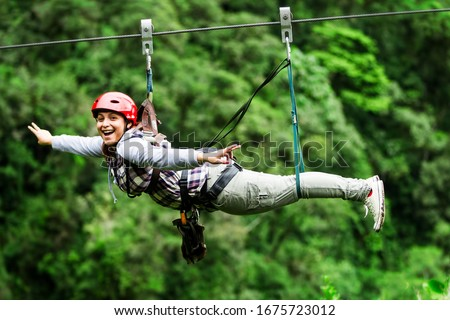 mature visitor wearing informal suit on zipline trip selective stress against misty jungle excursion race zipline canopi vacation vegetation canopy outdoor expedition feminine rainforest ecuador fores Royalty-Free Stock Photo #1675723012