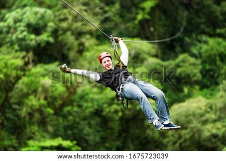 zipline canopy zip line wire adventure jungle forest sport flight mature masculine pilgrim wearing informal linen on zipline or canopi experience in ecuadorian rain forest zipline canopy zip line wire Royalty-Free Stock Photo #1675723039