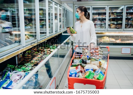 Woman wearing face mask buying in supermarket.Panic shopping during Coronavirus covid-19 pandemic.Budget buying at a supply store.Buying freezer smart purchased household pantry groceries