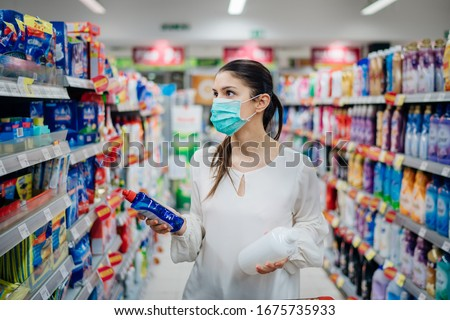 Woman wearing protective mask preparing for virus pandemic spread quarantine.Hygiene, cleaning and disinfection products.Preventive measures and protection.Supply shopping during the epidemic. #1675735933
