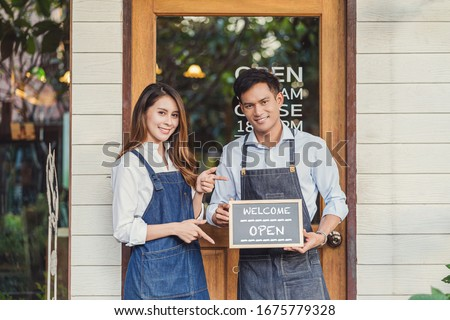 Closeup Asian partner Small business owner hands holding and showing the chalkboard with Welcome Open sign in front of coffee shop, startup with cafe store, installing open and close label concept #1675779328